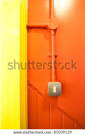 power switch on fresh orange and yellow wall