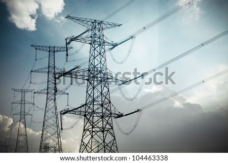 power tower silhouetted against blue sky and light clouds - stock photo