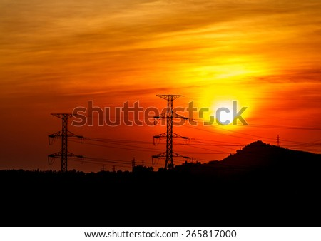 Power transmission line with the sun in the evening. - stock photo