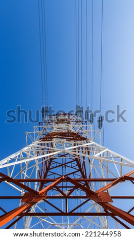 Power transmission lines against blue sky - stock photo