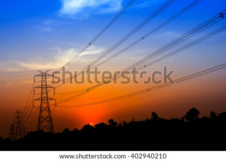 power transmission tower silhouetted against the sunset glow