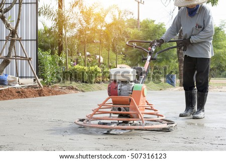 Power trowel machine and construction worker - concrete floor of polished concrete surface