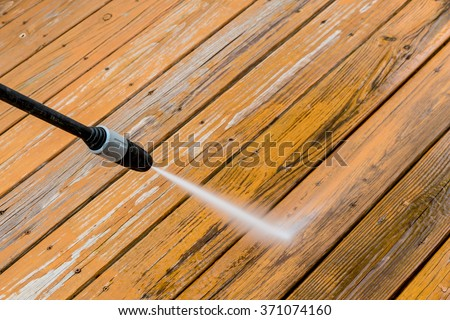 Power washing. Wooden deck floor cleaning with high pressure water jet. - stock photo
