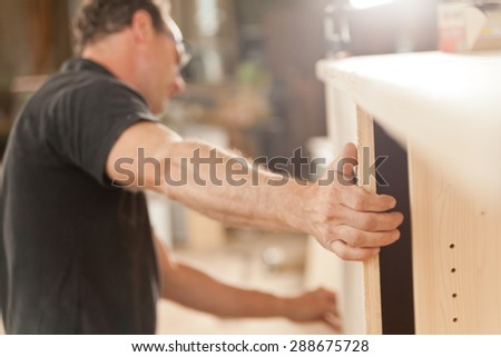 powerful arm and hand of a carpenter placing a component in a piece of handcrafted piece of furniture - stock photo