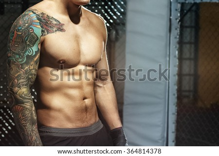 Powerful body. Cropped shot of a muscular toned torso of a tattooed fighter in octagon fighting cage - stock photo