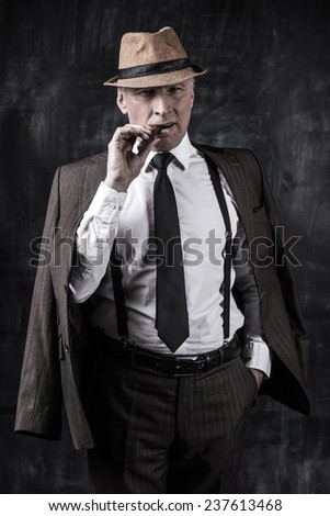 Powerful boss. Serious senior man in hat and suspenders smoking cigar and looking at you while standing against dark background  - stock photo