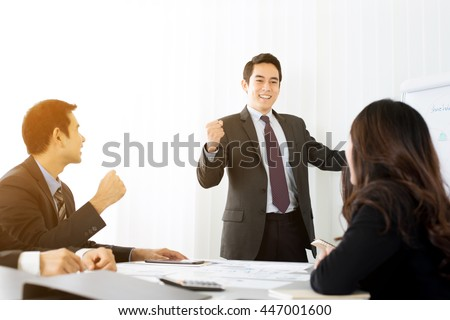 Powerful businessman clenching his fist empowering his colleagues in front of meeting room - stock photo