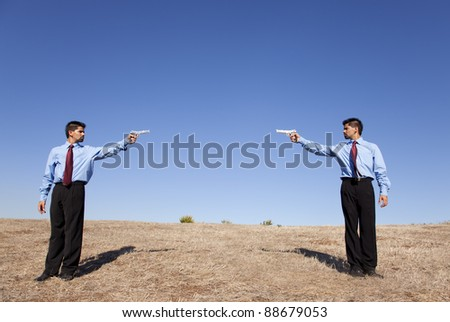 Powerful businessman making a duel with handguns in a field - stock photo