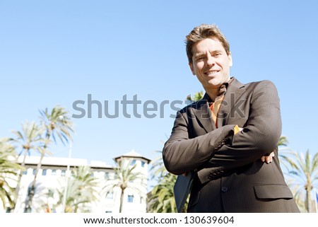 Powerful businessman standing in a classic architecture city holding a digital tablet pad with his arms crossed, smiling.