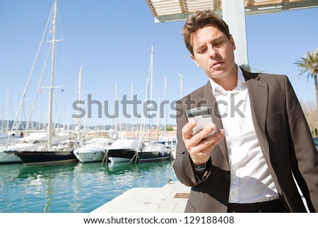 "Powerful businessman using his ""smart phone"" while standing near a marine with luxury yachts against a deep blue sky and sea."
