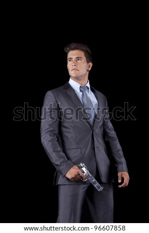 Powerful businessman with a gun (isolated on black)