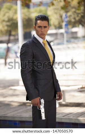 Powerful businessman with a gun on his hand - stock photo