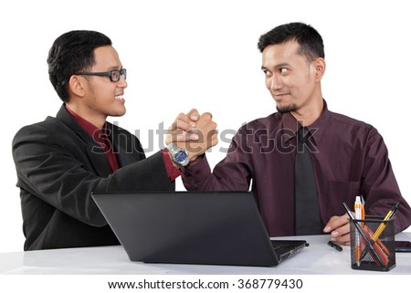 Powerful handshake of two confident businessmen looking at each other, isolated on white background - stock photo