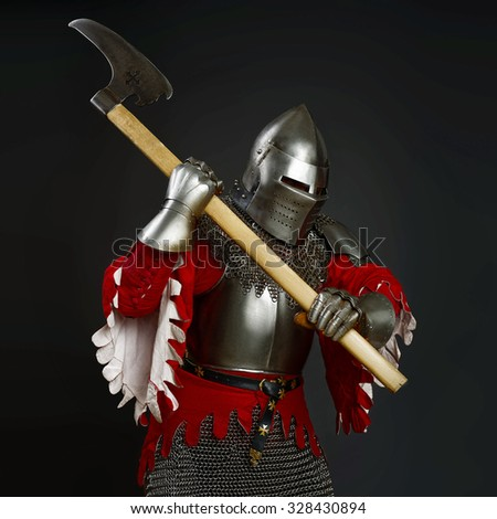 Powerful knight in the armor. Medieval knight in the field with an axe. Dark background. - stock photo