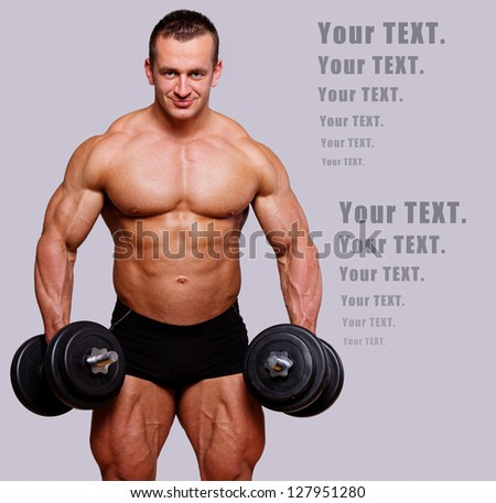 powerful man posing on a photoshoot with dumbbells - stock photo