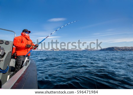 powerful man with a spinning rod in his hands. sea boat. fisherman
