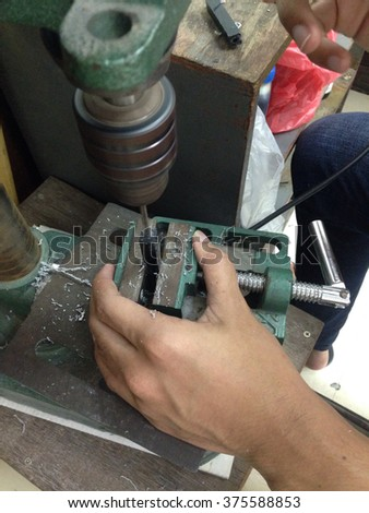 Powerful mechanic drilling in workshop.