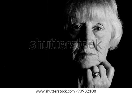 powerful monochrome low key image of a sad elderly woman