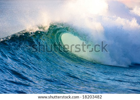 Powerful ocean wave lit by morning sun