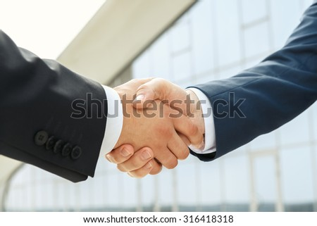 Powerful partnership supported by a handshake outdoors - stock photo