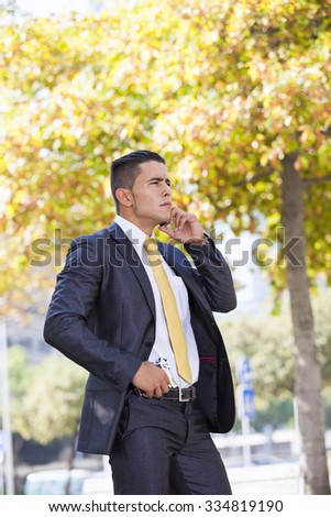 Powerful security businessman talking at his cellphone with a handgun in his belt
