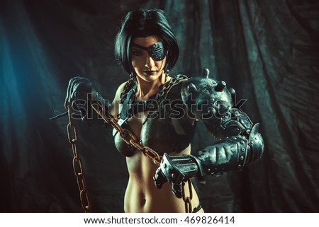 Powerful steam punk woman in metal lingerie is holding a chain.