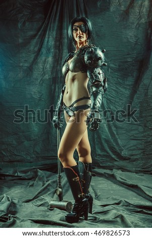 Powerful steam punk woman in metal lingerie with a heavy sledgehammer.
