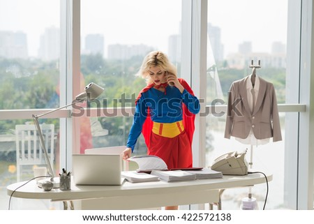 Powerful superwoman talking on phone and working with documents  in office - stock photo