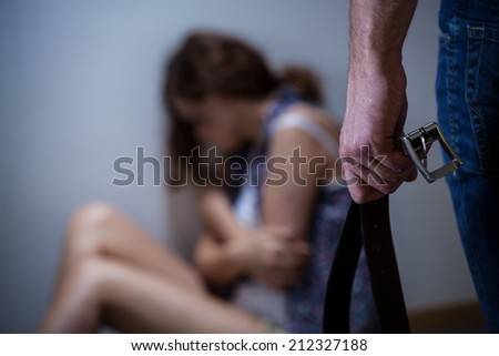 Powerful, violent husband with a belt, horizontal - stock photo