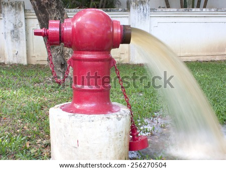 powerful water flow coming out with impetus from a street hydrant Red - stock photo
