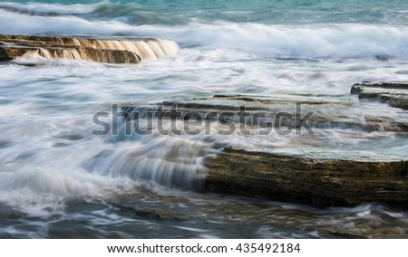 Powerful waves crashing with power on sea rock plates creating small waterfalls and smooth streams of water.  - stock photo