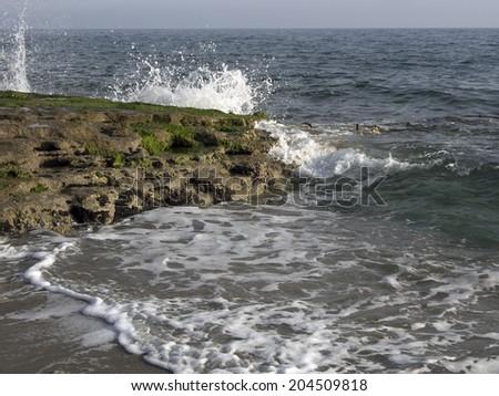 Powerful Waves crushing on a rocky beach - stock photo