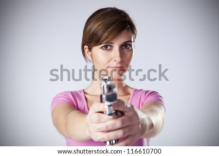 Powerful young woman with a gun - stock photo