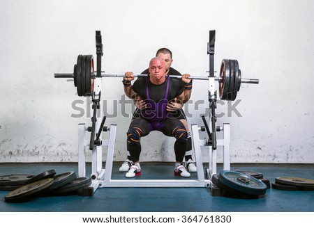 Powerlifter lifting weights helped by his master - stock photo