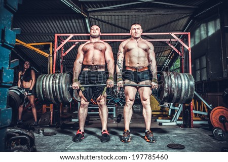 Powerlifter with strong arms lifting weights - stock photo