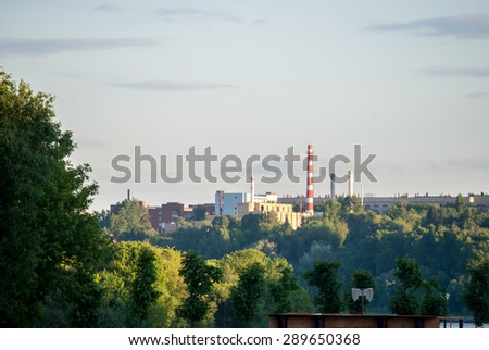 Powerplant seen in distance surrounded by nature. Symbol of Technology, pollution and urbanism - stock photo