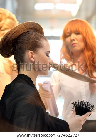 POZNAN - APRIL 18: Hairdresser arranging hairdo using hairspray at The Look Beauty Vision Poznan 2015 on April 18, 2015 in Poznan, Poland.