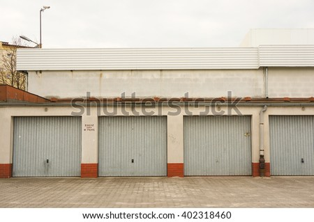 POZNAN, POLAND - APRIL 07, 2016: Row of garages with locked doors on a cloudy day - stock photo