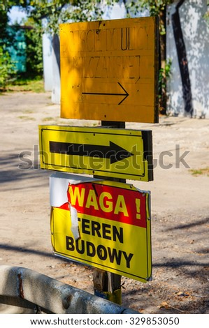 POZNAN, POLAND - AUGUST 29, 2015: Attention and direction signs on wooden pole