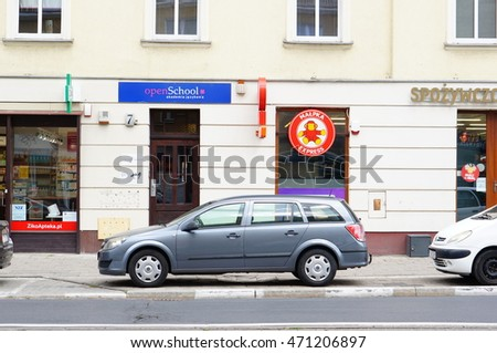 POZNAN, POLAND - AUGUST 11, 2016: Car parked in front of open school and Malpa grocery store
