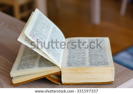 POZNAN, POLAND - AUGUST 29, 2015: Dictionary in Polish and English language on wooden table