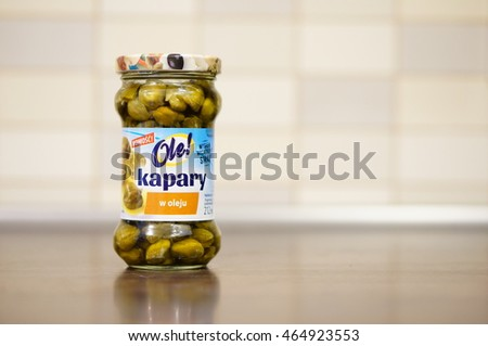 POZNAN, POLAND - AUGUST 07, 2016: Polish Ole capers in a glass jar on wooden table