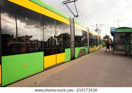 POZNAN, POLAND - AUGUST 22, 2013: Tram arrival at the bus stop in the Jan Pawla II street - stock photo