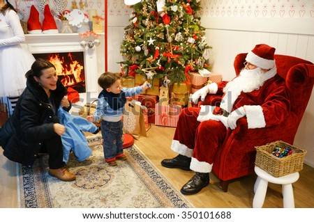 POZNAN, POLAND - DECEMBER 06, 2015: Mother and two years old boy by sitting Santa Claus in the Galeria Malta shopping mall - stock photo