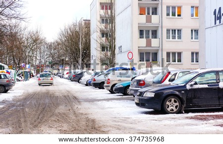 POZNAN, POLAND - DECEMBER 08, 2013: Parked cars by a apartment blocks in the winter season - stock photo