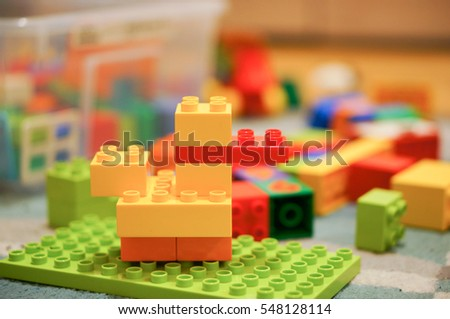 POZNAN, POLAND - DECEMBER 02, 2016: Yellow plastic toy duck made of Lego Duplo blocks lying on a floor in soft focus