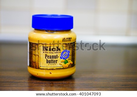 POZNAN, POLAND - FEBRUARY 26, 2016: Nick peanut butter in a plastic jar on wooden table