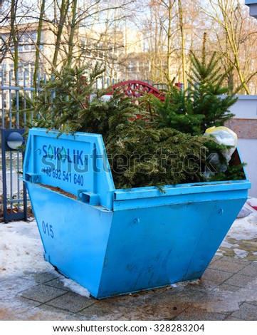 POZNAN, POLAND - FEBRUARY 01, 2014: Old christmas tree in a blue metal waste container - stock photo