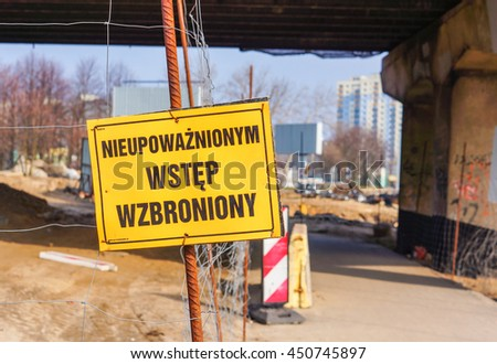 POZNAN, POLAND - FEBRUARY 28, 2016: Yellow warning sign in front of a construction area next to footpath