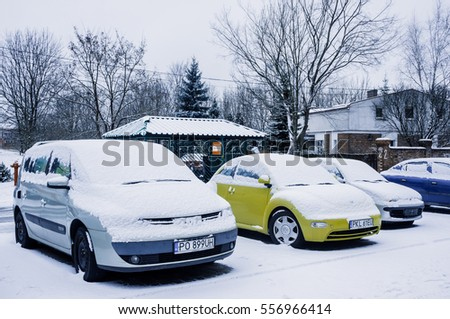 POZNAN, POLAND - JANUARY 15, 2017: Row of parked cars covered with snow on a cold winter day
